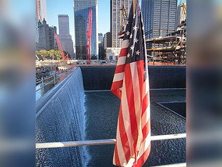 The World Trade Center memorial with an American flag in front.