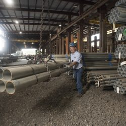 A worker lifts pipes with a chain