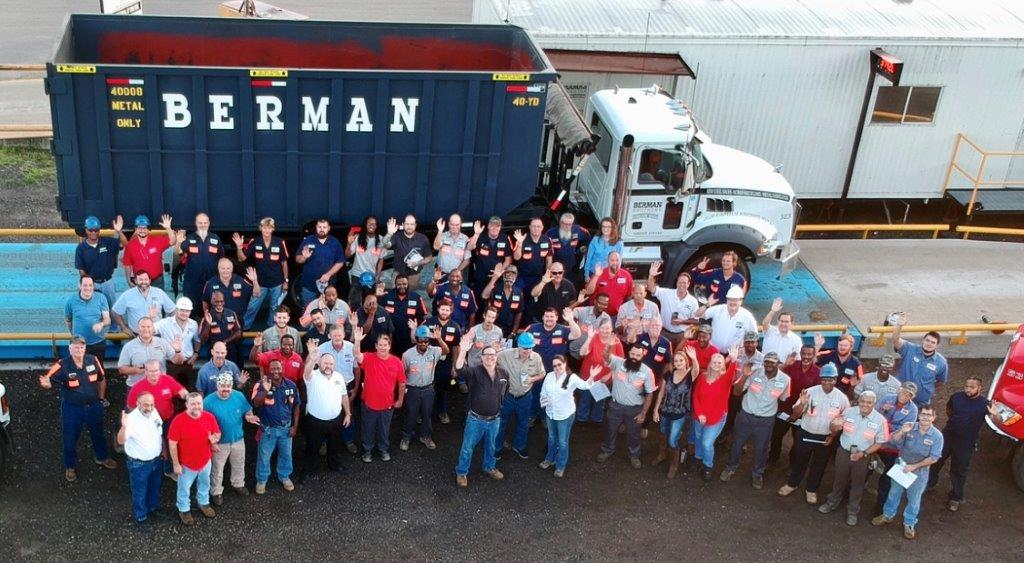 The Berman Bros team stands in front of a truck while smiling and waving.